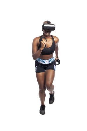 Black African American female running in VR while wearing a virtual reality headset for training or playing a video game.  Depicts technology and sport and esports. Stock fotó