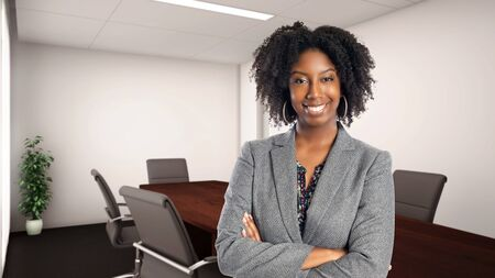 Black African American businesswoman in an office looking confident or arrogant.  She is an owner or an executive of the workplace.  Depicts careers and startup business. Stockfoto