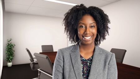 Black African American businesswoman in an office smiling happy.  She is an owner or an executive of the workplace.  Depicts careers and startup business. 스톡 콘텐츠