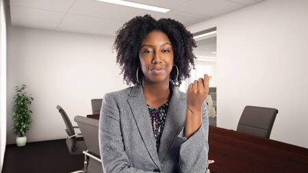 Black African American businesswoman in an office doing a money gesture.  She is an owner or an executive of the workplace.  Depicts careers and startup business.