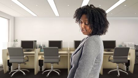 Black African American businesswoman in an office looking shy.  She is an owner or an executive of the workplace.  Depicts careers and startup business.