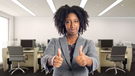 Black African American businesswoman in an office with thumbs up. She is an owner or an executive of the workplace. Depicts careers and startup business.