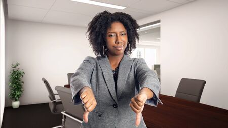 Black African American businesswoman in an office with thumbs down.  She is an owner or an executive of the workplace.  Depicts careers and startup business. Banco de Imagens