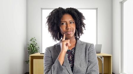 Empresaria afroamericana negra en una oficina pensando en ideas. Ella es propietaria o ejecutiva del lugar de trabajo. Representa carreras y empresas emergentes.