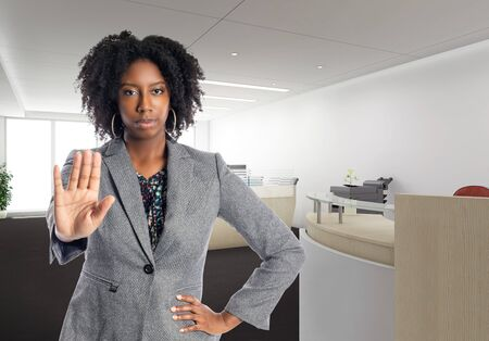 Black African American businesswoman in an office with a stop gesture.  She is an owner or an executive of the workplace.  Depicts careers and startup business. Banco de Imagens