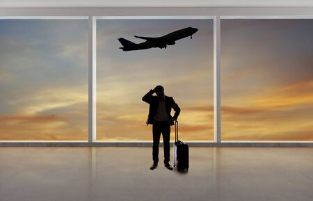 Silhouette of a traveling businessman with luggage in front of an airport window with a view of the sky and an airplane.  The panorama has copy space for text.  Depicts business travel.