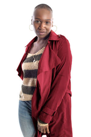 Black African American fashion model with bald hairstyle confidently posing with a coffee brown colored jacket for fall collection. Depicts fashion design and clothing apparel