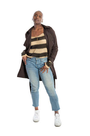 Black African American fashion model with bald hairstyle confidently posing with a coffee brown colored jacket for fall collection. Depicts fashion design and clothing apparel Reklamní fotografie