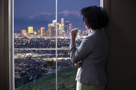 Black female business woman looking out the window of an office in Los Angeles. She looks like a female architect thinking of urban development or a city mayor or governor planning zoning laws.