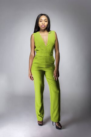 African American fashion model posing with lime green v-neck jumpsuit in a studio for fall collection catalog.  She is confidently showing the sleeveless top and matching pants. 免版税图像