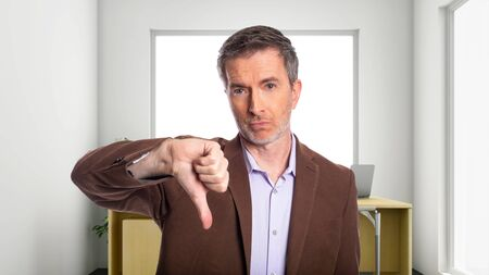 Middle-Aged businessman with gray hair and wearing a brown jacket standing in an office.  Depicts startup and corporate business.  He is holding thumbs down in disapproval.