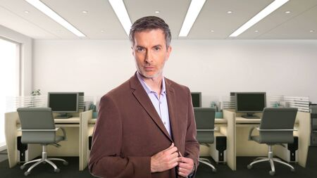 Middle-Aged businessman with gray hair and wearing a brown jacket standing in an office. Depicts startup and corporate business. He is looking confident or arrogant. Stock Photo