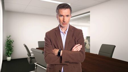 Middle-Aged businessman with gray hair and wearing a brown jacket standing in an office.  Depicts startup and corporate business.  He is doubtful or unsure.