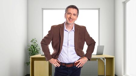 Middle-Aged businessman with gray hair and wearing a brown jacket standing in an office.  Depicts startup and corporate business.  He is smiling and happy.