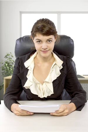 Young female business employee newly hired or a student doing writer internship.  She is in a workstation in a corporate office holding paper documents. Stock Photo - 131212842