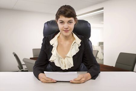 Young female business employee newly hired or a student doing writer internship.  She is in a workstation in a corporate office holding paper documents.