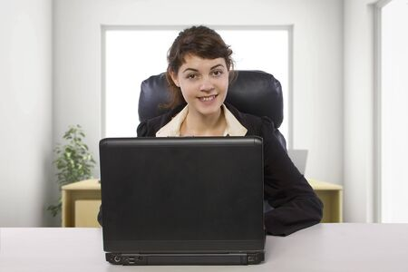 Young female business employee newly hired or a student doing writer internship.  She is in a workstation in a corporate office typing on a computer.
