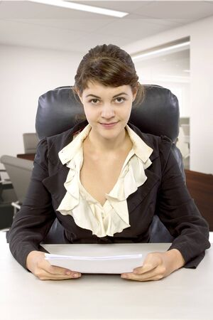 Young female business employee newly hired or a student doing writer internship.  She is in a workstation in a corporate office holding paper documents. Stock Photo - 131212821