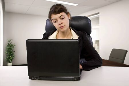 Young Caucasian female intern looking tired or stressed out in an office desk.  She is doing an unpaid internship and looking worried about student loan debt.