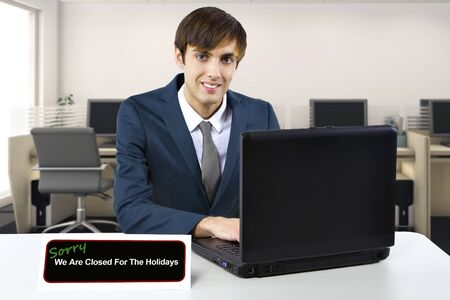 Businessman on a desk with a closed sign using a computer to type a vacation auto reply email.  He is finished with work for the holidays and closing the office. Banque d'images