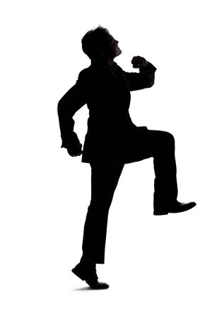 Full body silhouette of a businessman isolated on a white background. He is in a walking gesture and moving by taking a step forward