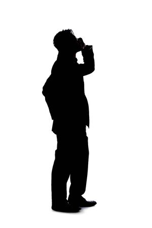 Full body silhouette of a businessman isolated on a white background. He is using a cell phone or mobile device to talk or send messages.