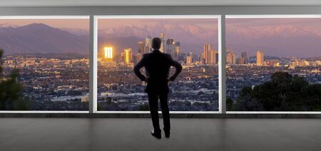 Empresario vistiendo un traje mirando los edificios del centro de Los Ángeles desde la ventana de una oficina. El hombre parece un político como un alcalde, un arquitecto o un desarrollador inmobiliario que trabaja en Los Ángeles. Foto de archivo