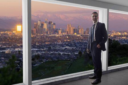 Empresario vistiendo un traje mirando los edificios del centro de Los Ángeles desde la ventana de una oficina. El hombre parece un político como un alcalde, un arquitecto o un desarrollador inmobiliario que trabaja en Los Ángeles.