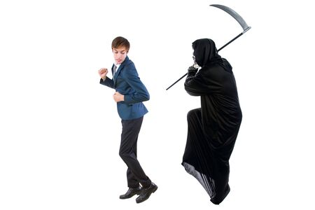 Man in a Halloween grim reaper ghost costume chasing, mocking and making fun of scared businessman running away. Can also depict death following a man as a metaphor for life insurance.