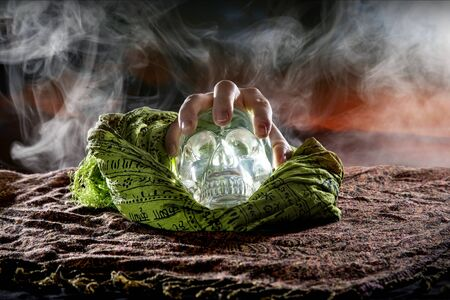 Hand grabbing a scary or creepy glowing crystal skull on Halloween holiday or Dia De Los Muertos Day of the Dead festival.  Depicts horror theme and superstition.