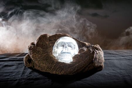 Scary or creepy glowing crystal skull on Halloween holiday or Dia De Los Muertos Day of the Dead festival.  Depicts horror theme and superstition.