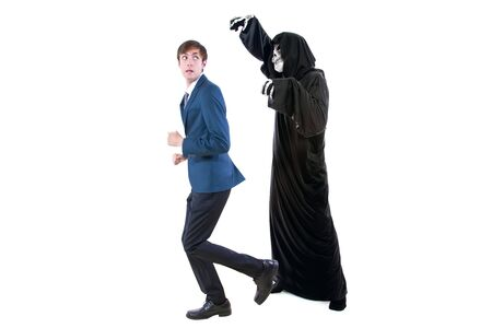 Man in a Halloween grim reaper ghost costume chasing, mocking and making fun of scared businessman running away.  Can also depict death following a man as a metaphor for life insurance. Stock Photo