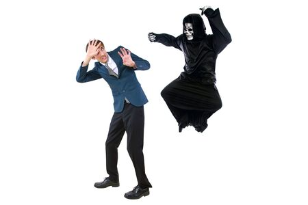 Man in a Halloween grim reaper ghost costume chasing, mocking and making fun of scared businessman running away.  Can also depict death following a man as a metaphor for life insurance. Banque d'images - 132382462