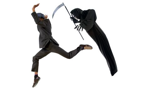 Man in a grim reaper halloween ghost costume having fun and scaring a grown businessman in a suit.  The image depicts pranks and being surprised.  Isolated on a white background.