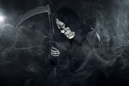 Scary looking grim reaper ghost wielding a scythe or sickle coming out of the fog.  The haunting monster depicts death and evil and is a common Halloween theme.  Stock Photo