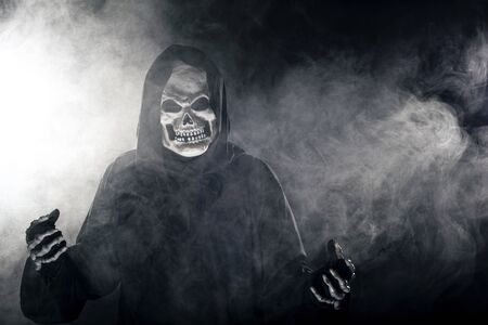 Scary looking grim reaper ghost coming out of the foggy mist.  The haunting creepy demon depicts death and evil and is a common Halloween theme as well as Day of the Dead.