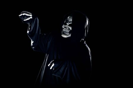 Scary monster or grim reaper ghost coming out of the dark shadows to haunt during Halloween.  Depicts a scary and deadly fictitious demon Stock Photo