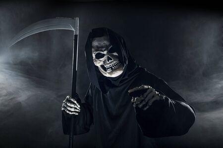 Beängstigend aussehender Sensenmann-Geist, der eine Sense oder Sichel schwingt, die aus dem Nebel kommen. Das eindringliche Monster stellt Tod und Böses dar und ist ein häufiges Halloween-Thema. Standard-Bild