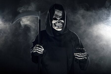 Scary looking grim reaper ghost wielding a scythe or sickle coming out of the fog.  The haunting monster depicts death and evil and is a common Halloween theme.