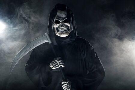 Beängstigend aussehender Sensenmann-Geist, der eine Sense oder Sichel schwingt, die aus dem Nebel kommen. Das eindringliche Monster stellt Tod und Böses dar und ist ein häufiges Halloween-Thema.