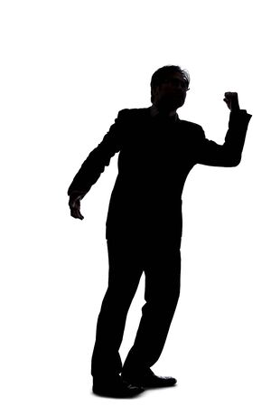Silhouette of a backlit model posing as a businessman on a white background.  He is punching out of anger with his fists.