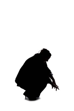 Silhouette of a curvy or plus size businesswoman on a white background for composites. She is looking for something on the ground Archivio Fotografico