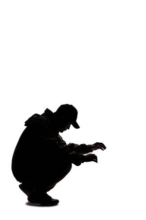 Silhouette of a male hiker or explorer isolated on a white background wearing a hat and clothes for trekking. He is searching or looking for something on the ground Stock Photo