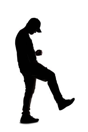 Silhouette of a man wearing casual clothes isolated on a white background. He is kicking something 写真素材