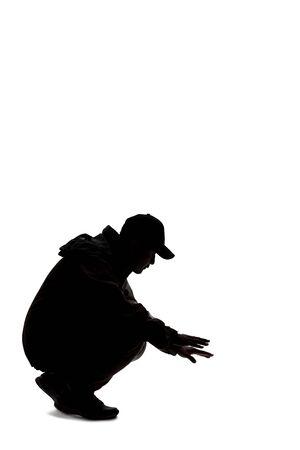 Siluetta di un escursionista maschio o esploratore isolato su uno sfondo bianco che indossa un cappello e vestiti per il trekking. Sta cercando o cerca qualcosa per terra