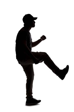 Silhouette of a man wearing casual clothes isolated on a white background. He is kicking something Stock Photo