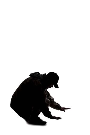 Silhouette of a male hiker or explorer isolated on a white background wearing a hat and clothes for trekking. He is searching or looking for something on the ground