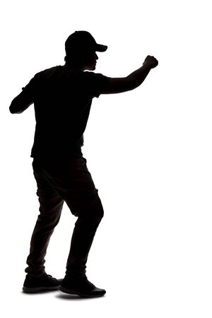 Silhouette of a man wearing casual clothes isolated on a white background. He is punching and hitting something