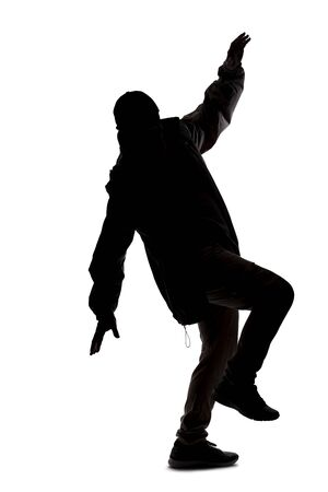 Silhouette of a male hiker or explorer isolated on a white background wearing a hat and clothes for trekking. He is falling or off balance Banco de Imagens