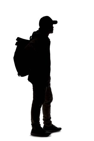 Silhouette of a man hiking and carrying a backpack on a white background. The isolated side view man can be used for composites. Depicts adventure and exploration. Reklamní fotografie